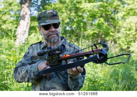 Hunter holding a crossbow while in the woods.