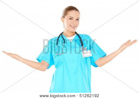 Smiling woman doctor in green scrubs standing raising her hands to the sides to indicate and include her surroundings  isolated on white