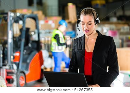 Friendly Woman, dispatcher or supervisor using headset and laptop at warehouse of forwarding company, smiling, a forklift is in Background
