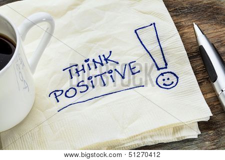 think positive - motivational slogan on a napkin with a cup of coffee