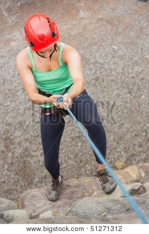 Sporty girl abseiling down rock face wearing red helmet