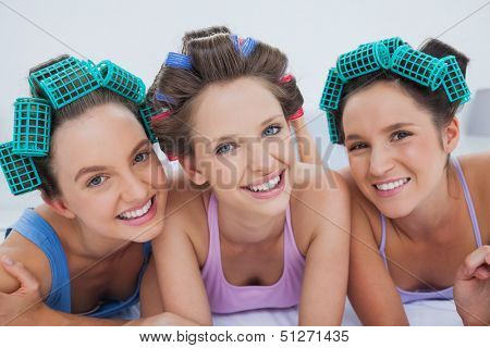 Friends in hair rollers and pajamas lying in bed and smiling at camera at sleepover