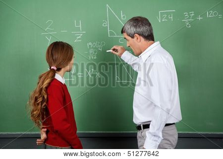 Side view of male professor teaching mathematics to female student on board in classroom