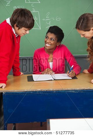 High school teenage students with young teacher at desk in classroom