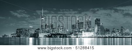 Toronto cityscape panorama at night over lake in black and white.
