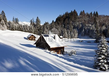 Very Detailed Photo Of A Sunny Winter Landscape With Occupied And Heated Log Cabins In The Mountains