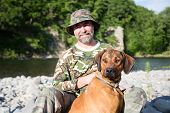 Traveler with a Rhodesian Ridgeback by the river. poster