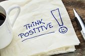 think positive - motivational slogan on a napkin with a cup of coffee poster