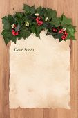 Letter to santa claus on old parchment paper with border of holly, ivy and mistletoe over oak background. poster