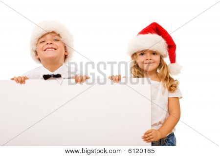 Happy Kids With Santa Hats And White Cardboard