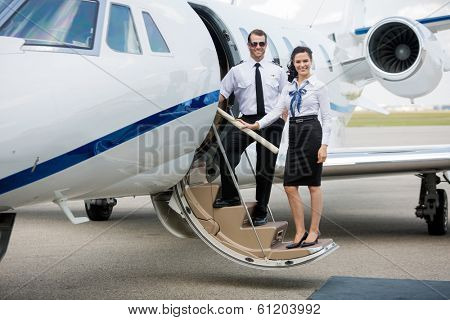 Full length portrait of confident airhostess and pilot standing on private jet's ladder at airport terminal poster