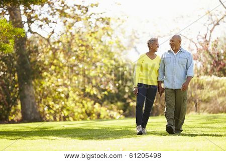 Senior Couple Walking Through Autumn Woodland