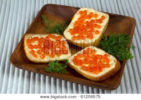 Three Sandwiches With Red Caviar On Wooden Plate