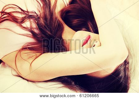 Sad woman is lying in bed with her arm on head and eyes. Young woman with long hair, wears pink underwear.