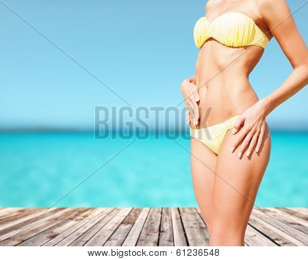 beach, vacation, summer holidays and body concept - closeup of female body in bikini at beach