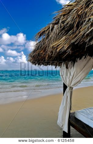 A bed lounger on a white sand beach in the caribbean poster