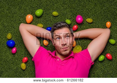 man lying green grass springtime with easter eggs