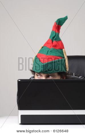 Man Hiding Behind Laptop With Elf Hat