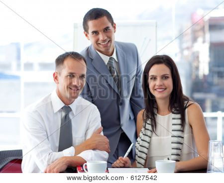 Young business people working together in office and smiling at the camera poster