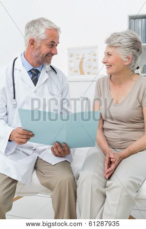 Portrait of a male doctor and senior patient with reports at medical office