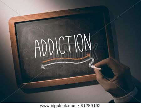 Hand writing the word addiction on black chalkboard