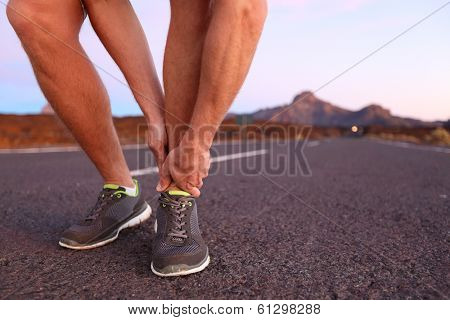Twisted angle - running sport injury. Male athlete runner touching foot in pain due to sprained ankle.
