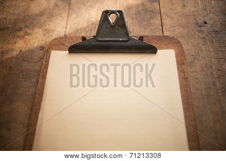 An vintage clipboard on a old wooden table, with blank old white paper.  Focus is on the writing area.