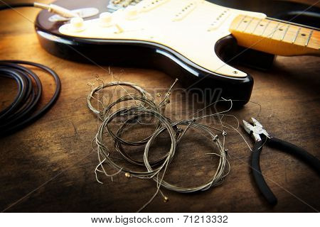 Guitar maintenance. Rolled old guitar strings and an electric guitar. Changing guitar strings. poster