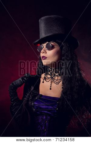 Vampire gothic girl in tophat and round eyeglasses, studio shot with smoke background