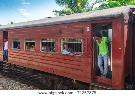 HIKKADUWA, SRI LANKA - MARCH 12, 2014: Local commuters in old train. Trains are very cheap and poorly maintained but it's the best option to witness a bit of everyday local life.