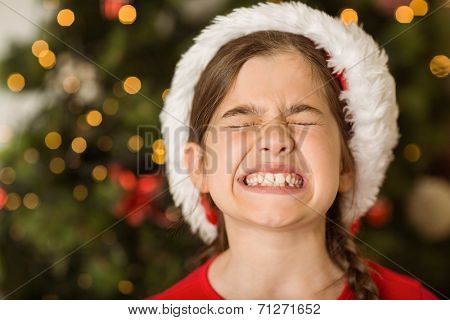 Festive little girl scrunching up her face at home in the living room