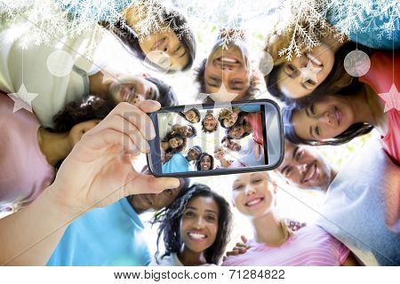 Hand holding smartphone showing friends forming huddle poster