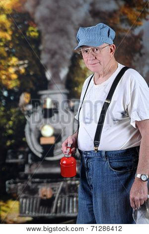 A senior RR engineer holding his oil can and rag while waiting for the steam engine nearby to stop.