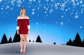 Pretty girl smiling in santa outfit against snow falling on fir tree forest poster