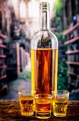 Bottle and three glass shots with yellow liqour resembling whiskey, rum, tequila, spirit on wooden table poster