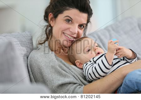 Cheerful mother cuddling in sofa with baby son