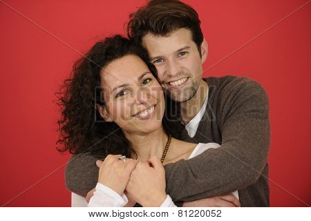 Studio shot: Portrait of happy man and woman on red background