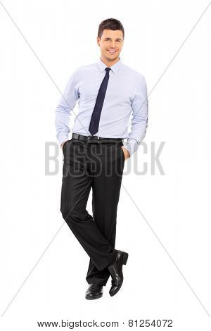 Full length portrait of a casual young businessman leaning against a wall isolated on white background
