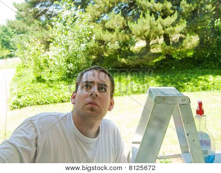 Man Looking Up At Window On Ladder