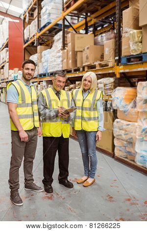Warehouse team working together wile smiling at camera in a large warehouse