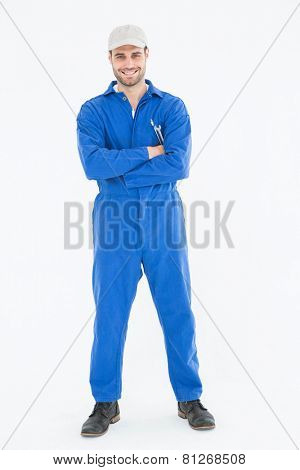 Full length portrait of confident young male mechanic standing arms crossed on white background