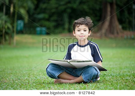 Young boy reading a book in the park