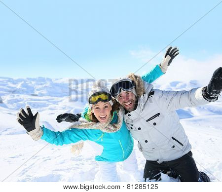 Cheerful couple of skiers having fun in the snow