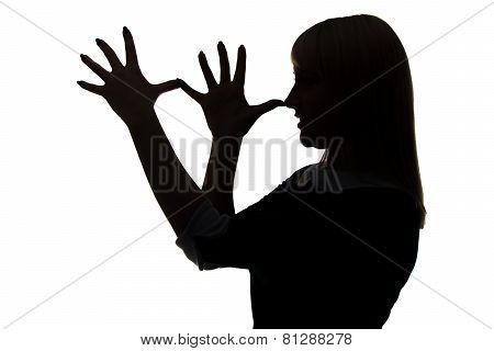 Silhouette of woman with palms on nose