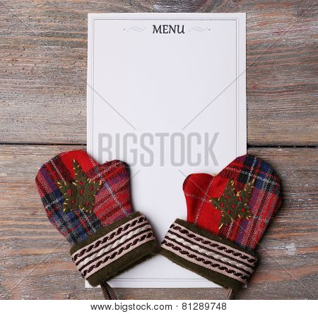 Menu sheet of paper with mittens on rustic wooden surface background