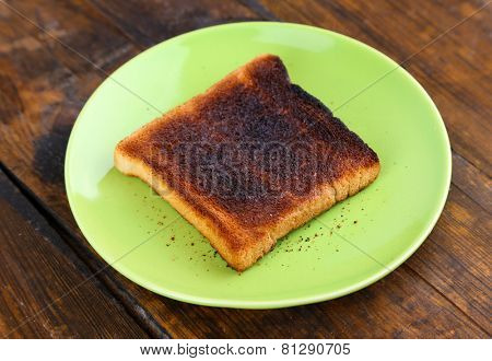 Burnt toast bread on light green plate, on wooden table background
