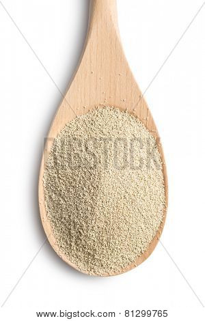 dry yeast in wooden spoon on white background