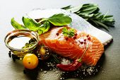 Delicious  portion of fresh salmon fillet  with aromatic herbs, spices and vegetables - healthy food, diet or cooking concept poster