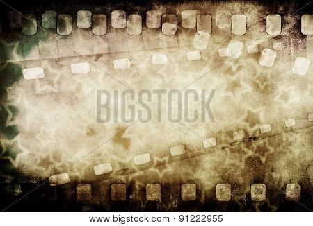 Grunge old motion picture reel with film strip and stars. Vintage background