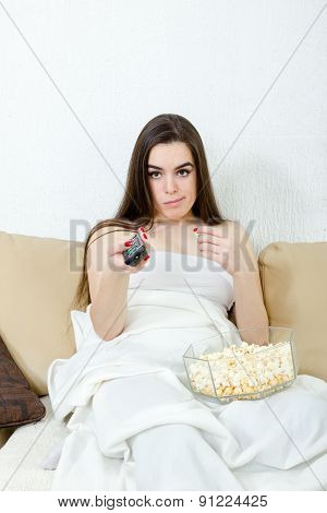 Young Girl Sitting On The Couch At Home And The List Of Programs On Tv With The Remote